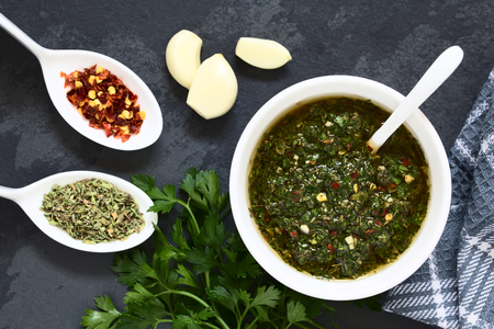 Photo pour Raw homemade Argentinian green Chimichurri or Chimmichurri salsa or sauce made of parsley, garlic, oregano, hot pepper, olive oil, vinegar, served in bowl, photographed overhead on slate with natural light (Selective Focus, Focus on the salsa) - image libre de droit