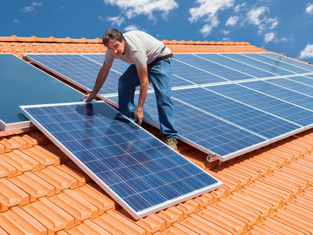 Photo pour Man installing alternative energy photovoltaic solar panels on roof - image libre de droit
