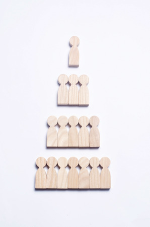 Photo for Wooden figures of people on a white background in the form of a pyramid of social hierarchy. The concept of relations in society and the company's business, collective. Political system. - Royalty Free Image