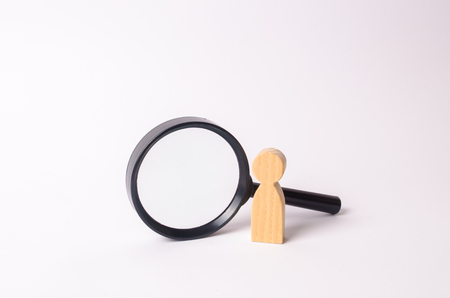 Photo for A wooden human figure stands near a magnifying glass on a white background. The concept of the search for people and workers. Search for vacancies and work. Human resources, management. - Royalty Free Image
