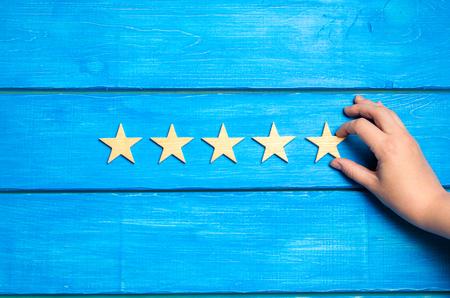 Foto de The hand puts the fifth star. The critic determines the rating of the restaurant, hotel, institution. - Imagen libre de derechos