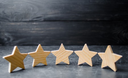 Foto de Five wooden stars. Get the fifth star. The concept of the rating of hotels and restaurants, the evaluation of critics and visitors. Quality level, good service. selective focus - Imagen libre de derechos