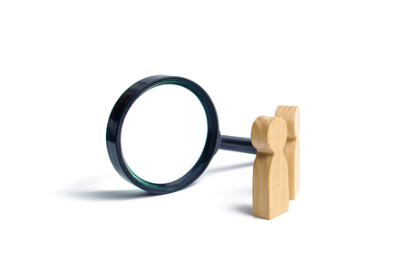 Photo for Two wooden human figure stands near a magnifying glass on a white background. The concept of the search for people and workers. Search for vacancies and work. Human resources, management. - Royalty Free Image