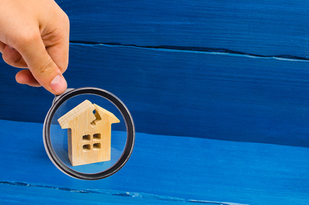 Photo for Magnifying glass is looking at the wooden house with a crack. The concept of a damaged house, dilapidated housing. Renovation, repair and restoration of the old building. Property insurance. - Royalty Free Image