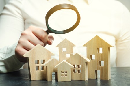 Foto de A woman is holding a magnifying glass over a wooden houses. Real estate appraiser. Property valuation / appraisal. Find a house. Search for housing. Real estate market analysis. Selective focus - Imagen libre de derechos