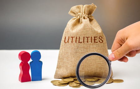 Foto de A money bag with the word Utilities and a family. The concept of saving money for the payment of utilities. The accumulation of money. A large debt. Electricity bill, heating. Debt repayment - Imagen libre de derechos