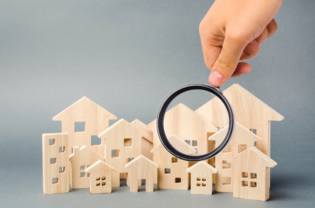 Foto de Wooden houses and magnifying glass. Property valuation. Home appraisal. Choice of location for the construction. House searching concept. Search for housing and apartments. Real estate - Imagen libre de derechos