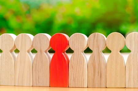 Foto de Wooden figures of people. The red man comes out with a team of workers. The concept of choosing a new leader. Choice of person. Hiring and recruiting. Human resource management. Selective focus - Imagen libre de derechos