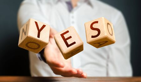 Photo for A man throws cubes with letters and makes up the word YES. Agreement and acceptance, answer the question. Courage and irresistibility, zeal forwards, consent. Confirmation and acceptance, approval - Royalty Free Image