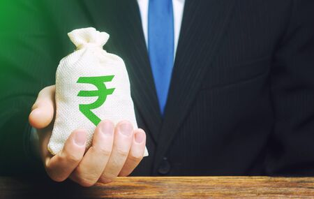 Photo for Man holds out a indian rupee money bag. Provision of money on credit, grant. Project financing. Payment purchases, profits dividends. Donations. Financial social assistance. Business investment - Royalty Free Image