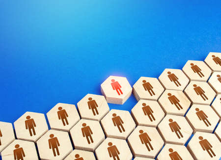 Foto de A person comes out of a group of people. Exit from mainstream society. Dismissal. Be different. Cooperation collaboration, joint efforts. Initiative. Expulsion from community. Talent, leadership. - Imagen libre de derechos