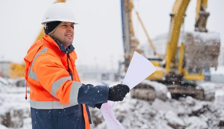 Foto de Civil engineer at construction site is inspecting ongoing works according to design drawings in difficult winter conditions - Imagen libre de derechos