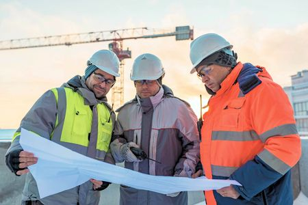 Photo pour Young Civil Engineers and Senior Foreman at construction site are inspecting ongoing production according to design drawings. - image libre de droit