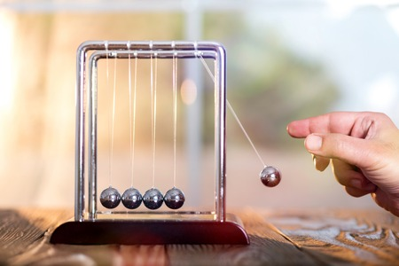 Foto de Concept For Action and Reaction or Cause And Result in Business With Newton's Cradle - Imagen libre de derechos