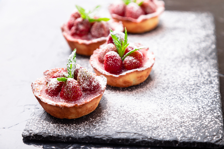 Foto de Homemade strawberries tarts with powdered sugar on slate plate, black background. Close up - Imagen libre de derechos