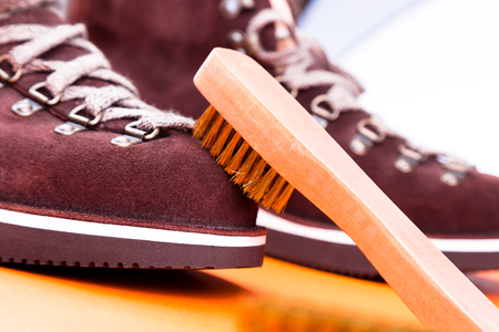 Photo pour Brown man suede boots with brush. Macro. Clean shoes. - image libre de droit