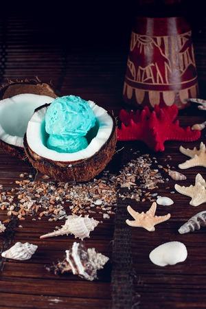 Photo for Blue ice cream in coconut bowl near sand, seashells, starfish. - Royalty Free Image