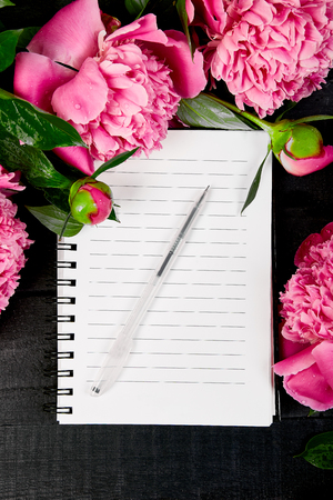 Photo pour Beautiful pink peony flowers on black background with note or diary. Planing to do list. Copy space Top view. Flat lay. Empty blank. - image libre de droit