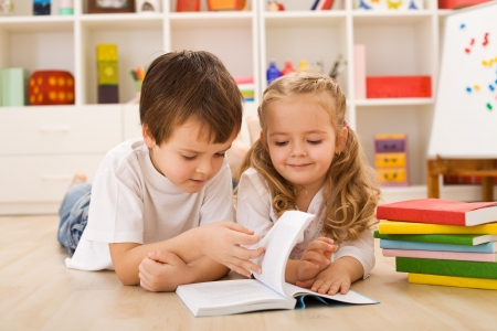 Photo for School boy laying on the floor teaching and showing her sister how to read - Royalty Free Image
