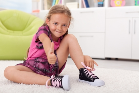 Photo for Little girl learning how to tie her shoes, being proud of herself - Royalty Free Image
