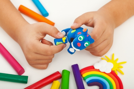 Photo pour Child playing with colorful clay making animal figures - closeup on hands - image libre de droit