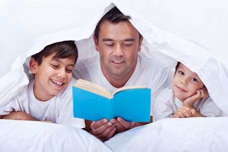 Photo pour Father reading a story to his little sons - family time together - image libre de droit