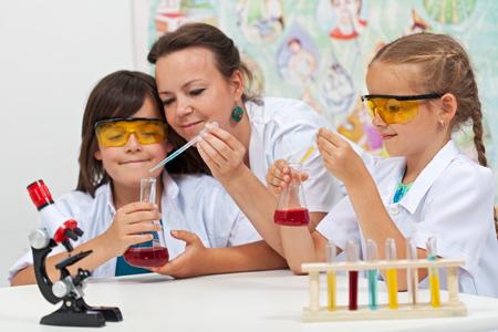 Foto de Chemical experiments in elementary school - kids helped by teacher in science class - Imagen libre de derechos