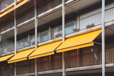 Foto de Nice balcony with yellow awning in apartment house. - Imagen libre de derechos