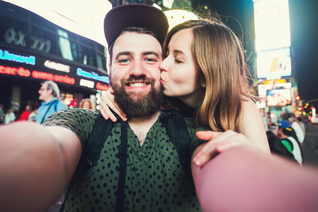 Photo for Happy dating couple in love taking selfie photo on Times Square in New York while travel across USA on honeymoon - Royalty Free Image