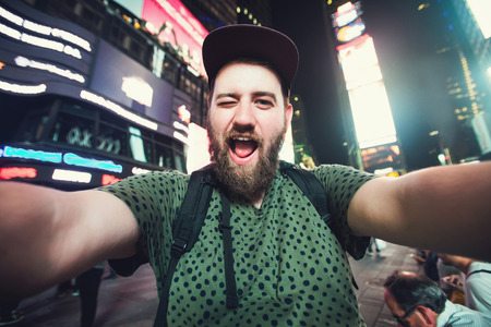 Foto für Funny bearded man backpacker smiling and taking selfie photo on Times Square in New York while travel alone across USA - Lizenzfreies Bild