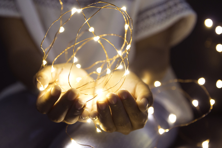 Foto de Woman hands holding string of lights in the dark to make a wish. - Imagen libre de derechos