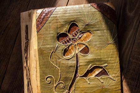 Foto de handmade photo album with flower on wooden background - Imagen libre de derechos