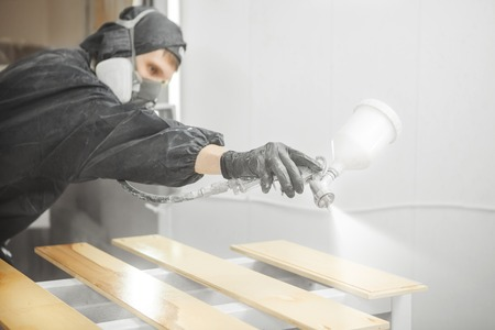 Photo for Man in respirator mask painting wooden planks at workshop. - Royalty Free Image