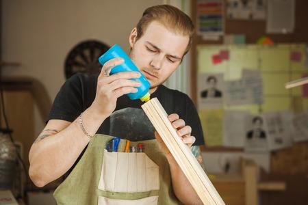Photo pour Male smear with glue wooden plank at workshop. Male working - image libre de droit