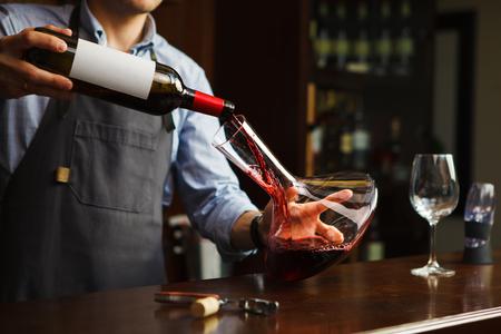 Foto de Sommelier pouring wine into glass from decanter. Male waiter - Imagen libre de derechos