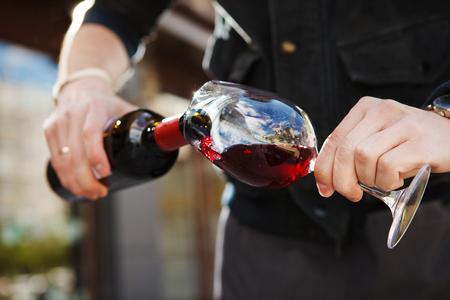 Foto de Man pouring wine into wineglass, male hand holding bottle of red expensive alcoholic beverage, closeup photo - Imagen libre de derechos