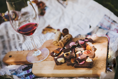 Foto de Glass with red wine and pieces of chocolate with nuts and raisins stands on cutting board on background of newspapers on the ground outdoors. Alcoholic drink in glassware with snacks - Imagen libre de derechos