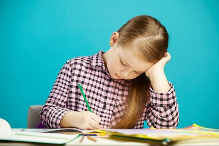 Foto de Horizontal shot of girl at desk carefully writes in notebook task, sitting over blue isolated background. Child performs homework. - Imagen libre de derechos