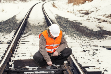 Railroad worker with adjustable wrench on the railroad