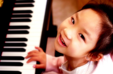 Top angle view of young girl playing piano