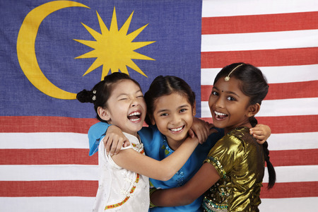 Foto de Happy girls hugging each other with Malaysian flag in the background - Imagen libre de derechos