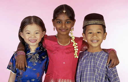 Photo pour Young Malay, Chinese and Indian kids in traditional clothes smiling and hugging each other - image libre de droit
