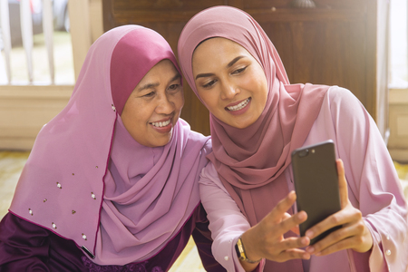 Photo for Malay woman taking self-photograph with her parent - Royalty Free Image