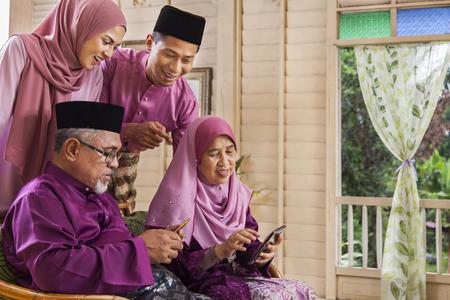 Foto de Muslim family looking at a mobile phone - Imagen libre de derechos