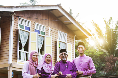 Photo pour Muslim family standing outside their house - image libre de droit