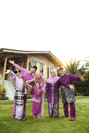 Foto per Muslim family standing outside their house - Immagine Royalty Free