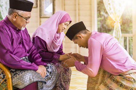 Photo pour Traditional act of respect in Muslim family on Eid al-Fitr - image libre de droit