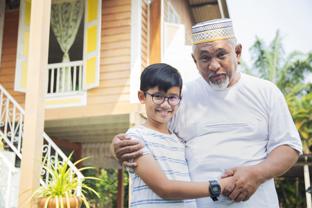 Foto de Boy with his grandfather in front of wooden house - Imagen libre de derechos