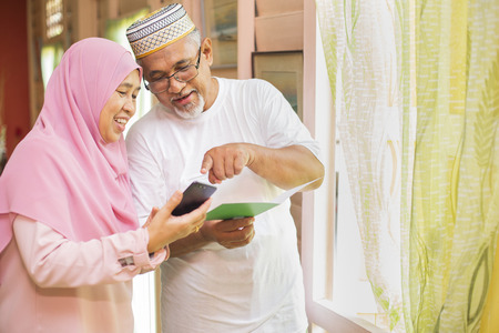 Photo pour Senior couple with an Eid greeting card looking at smartphone - image libre de droit