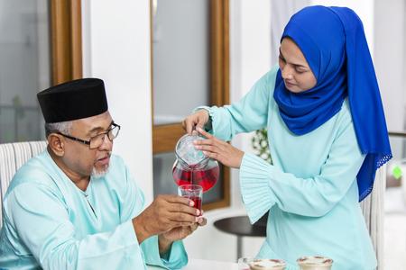 Photo pour Muslim woman serving beverage to her parent - image libre de droit
